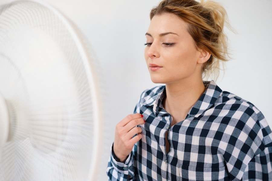 Woman trying to stay cool in front of a fan.