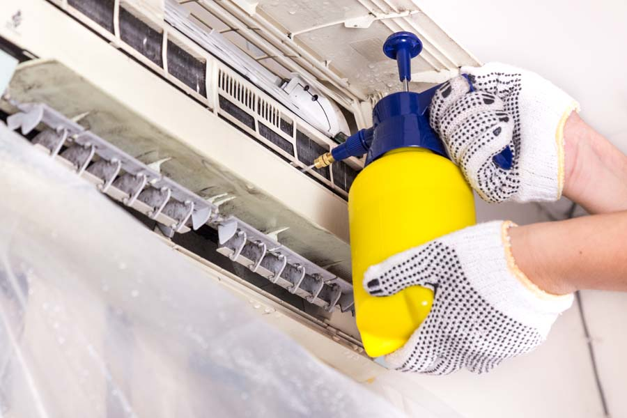 Technician Performing AC Maintenance Inspection Cleaning