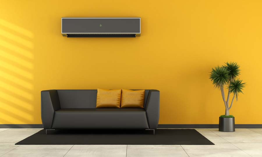 Modern living room with black couch and air conditioner on wall. Consider ductless AC.