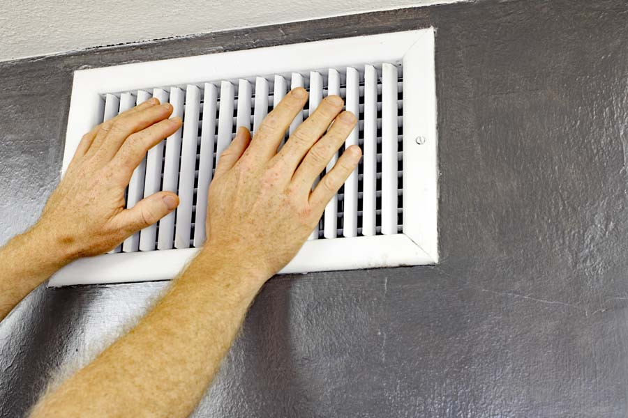 A pair of adult male hands feeling the flow of air coming out of an air vent on a wall near a ceiling. Man with hands in front of an air vent feeling for air flow. Why is my AC blowing hot air?