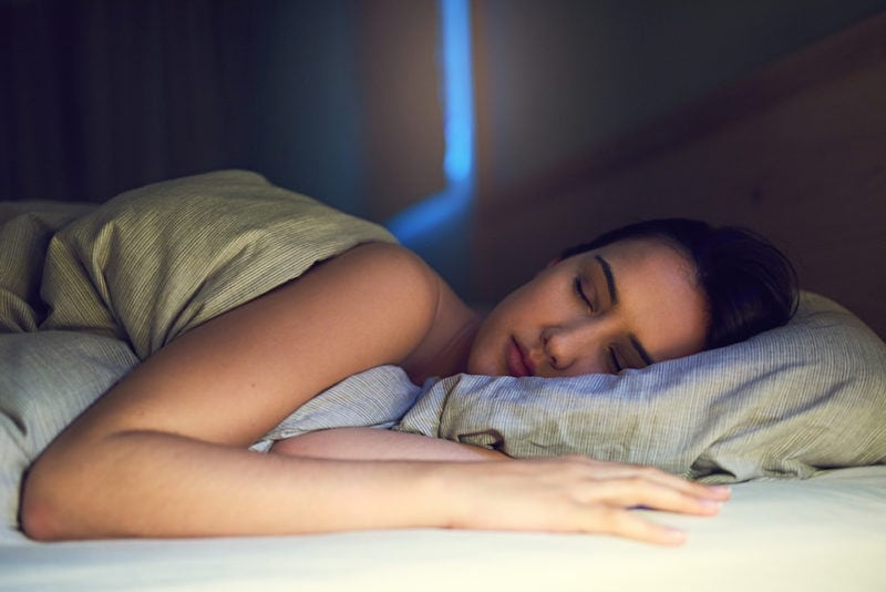 Shot of a young woman sound asleep in her bedroom ac sleep benefits