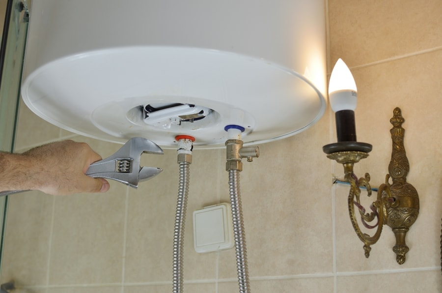 Everything You Need to Know About Boilers, Repairing a boiler with a wrench in a bathroom