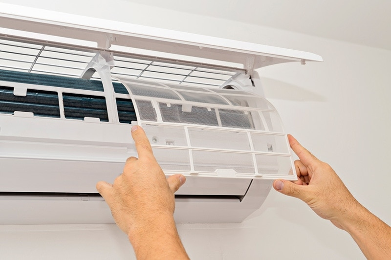 what maintenance is needed for a ductless system?, a pair of hands repairing a ductless system