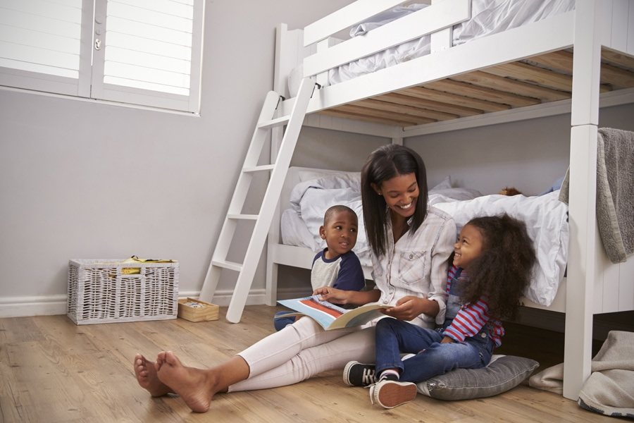 Mother Reading Story To Children In Their Bedroom while enjoying their good indoor air quality
