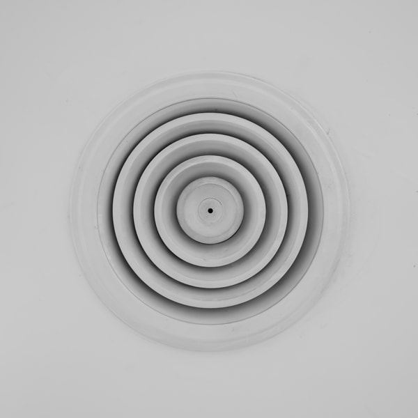 Air vent - circle metal frame on white ceiling. Leaky ducts and you.