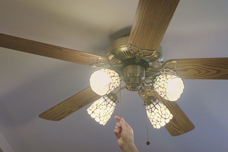 someone turning on their ceiling fan to save energy