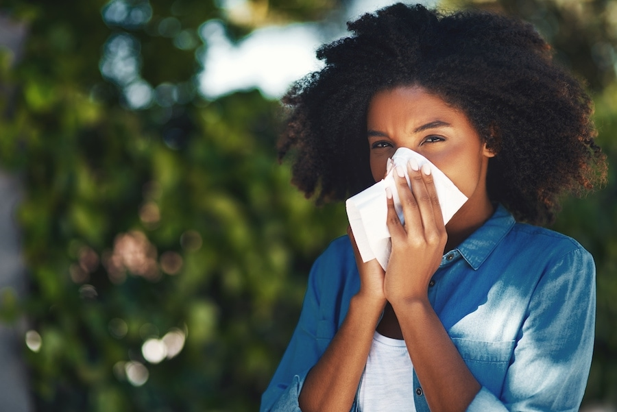Woman blowing nose outside due to allergy symptoms