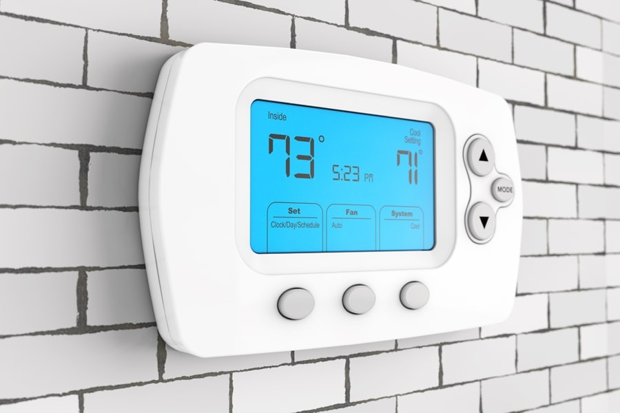 Programmable thermostat hung on a white brick wall.