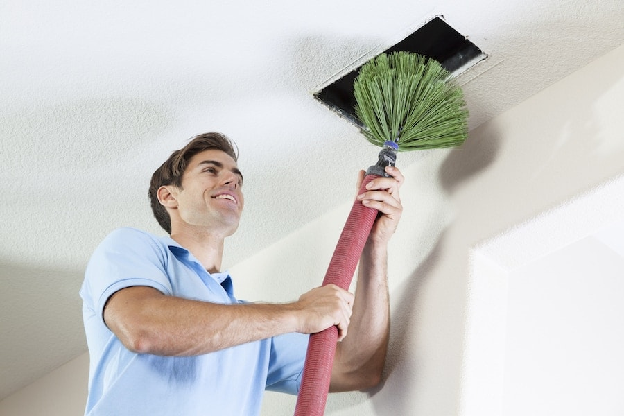 Man cleaning air ducts to eliminate mold